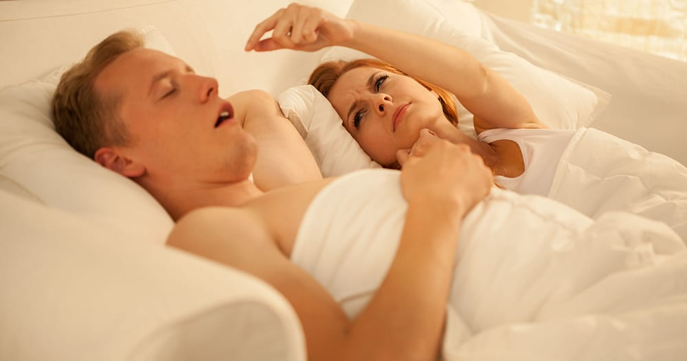 woman attempting to stop her husband from snoring