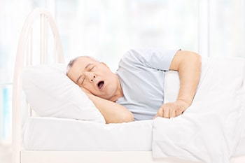 Mature man snoring in bed