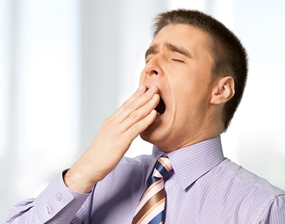 Sleep apnea treatment can help against daytime sleepiness like this man yawning while at work