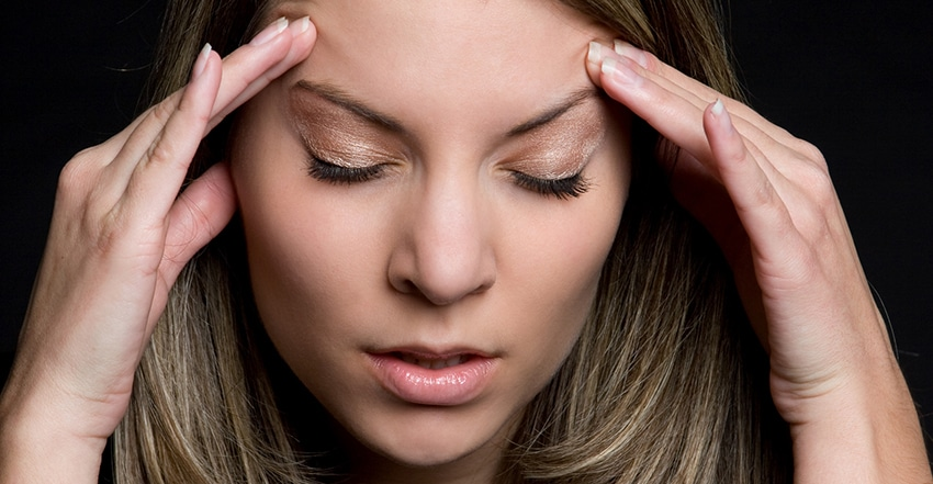 A young woman holding her head because of a TMJ related headache