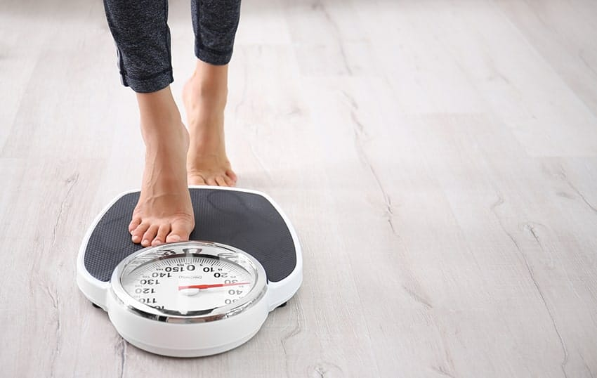 Woman checking her weight on a scale