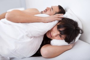 woman covering ears because her bed partner is snoring