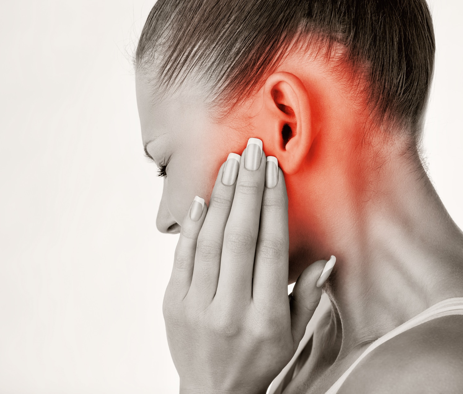 Young woman grasping ear in pain