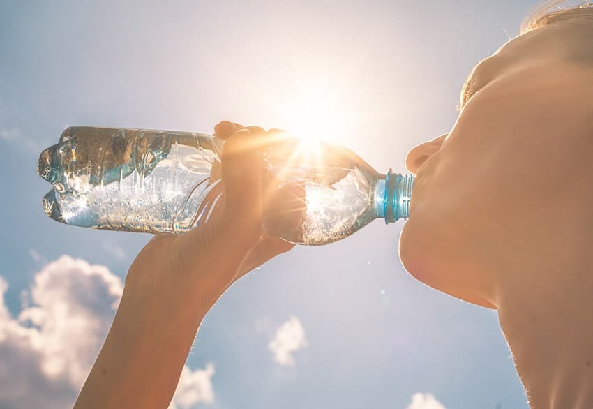 woman drinking water on a hot day to stay hydrated