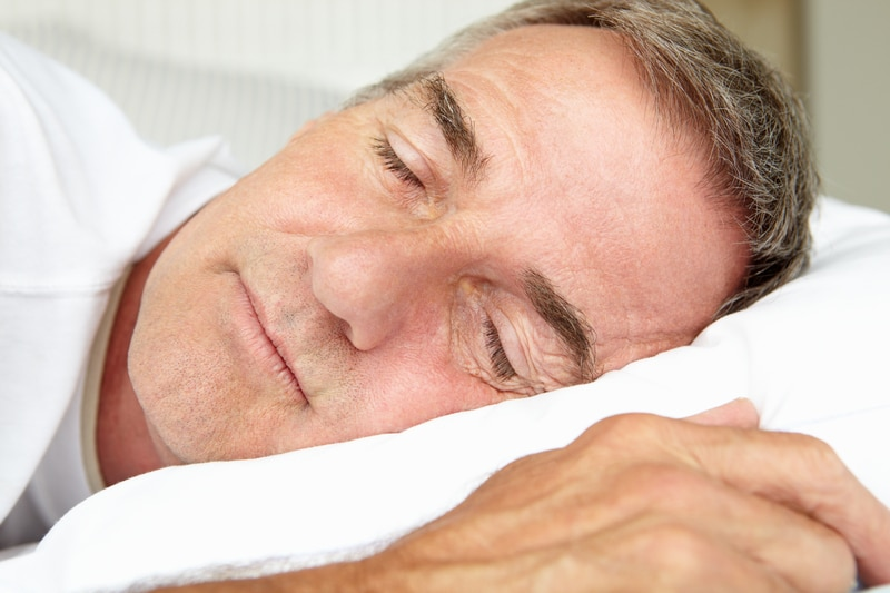 Middle aged man sleeping in a bedroon