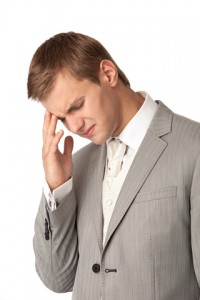Young business man standing with a white background, suffering from in a headache.