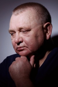 Middle aged man in a dark room, looking stressed