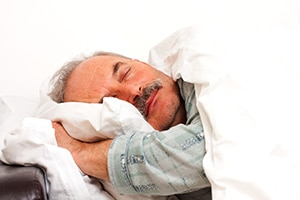 A senior man sleeping in bed.