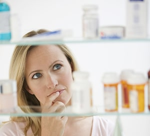 woman looking concerned while looking at medications
