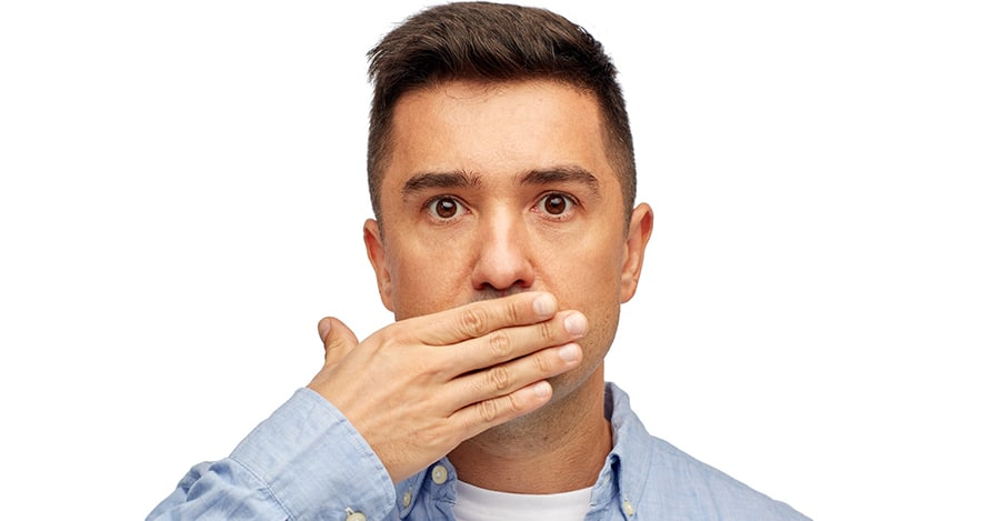 Man with bad breath covering his mouth