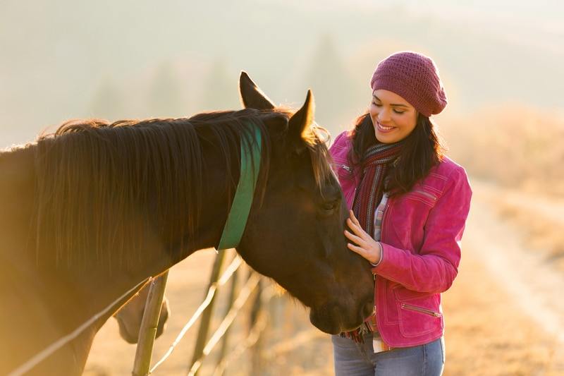 woman petting her horse