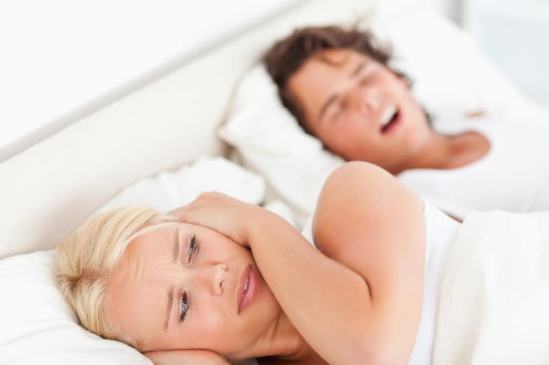 woman covering her ears while husband snores loudly next to her in bed