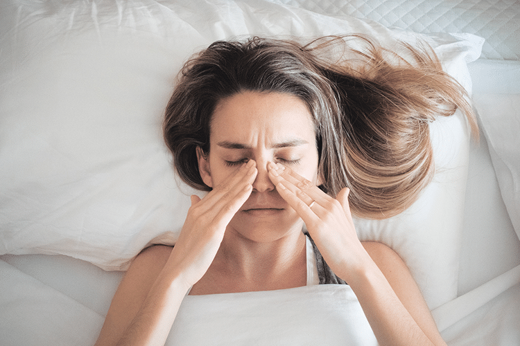 A young woman lying in bed holding her nose in pain