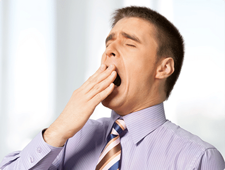 A man yawning while at work needs treatment for Sleep Apnea
