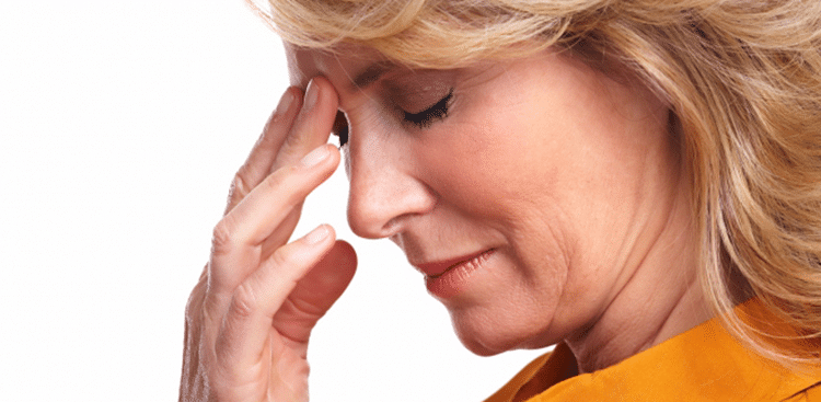 A middle aged woman holding her forehead because of pain