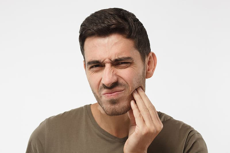 A man in pain holding his jaw, needing TMJ treatment and diagnosis.