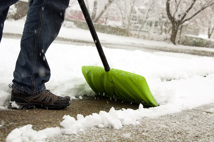 Brown shoe and blue jeans pushing green shovel in the snow to clear a path. Is the snow causing you headaches?