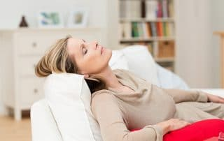 Older woman sleeping on a couch during the day. Is Sleep Apnea aging you prematurely?