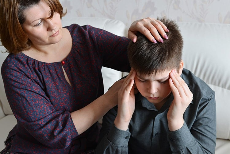Mother cares for her son who has migraine associated with TMJ. If I teen has TMJ, a study recommends a team treatment approach to improve results. This means that a neurologist should work with a doctor (or dentist) with expertise in orofacial pain. Cutting down the intensity and frequency of TMJ pain could lead to a responsive decrease in the intensity and frequency of migraines.