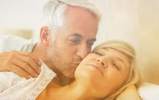 An older man kissing his wife on the cheek as they wake up in the morning. They are able to see the benefits of better rest with sleep apena treatment in Denver