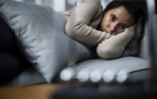 A woman suffering from depression stares blankly while lying in bed. Could Treating Sleep Apnea Help with Depression?