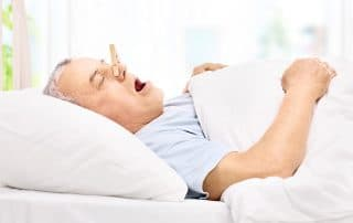 Senior sleeping with a clothespin on his nose, preventing him from snoring through his nose. There are other alternatives to this when you schedule a consultation with Denver Sleep Dentist Dr. Kevin Berry.
