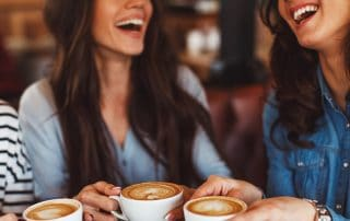Three young women enjoy coffee at a coffee shop. Sure, it tastes great and allows you time to talk, but is it causing you migraines?