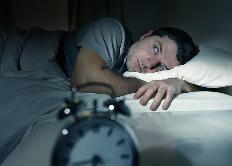 A man lays in bed in a lightly illuminated room, suffering from insomnia. Sleep disorders can be complex to treat are very commonly linked to sleep apnea.