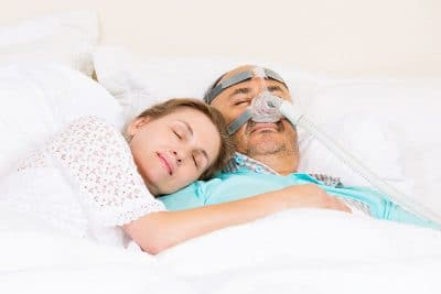 Man wearing a CPAP masks sleeps peacefully with his wife next to him.