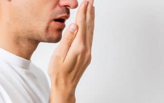 man checking his bad breath