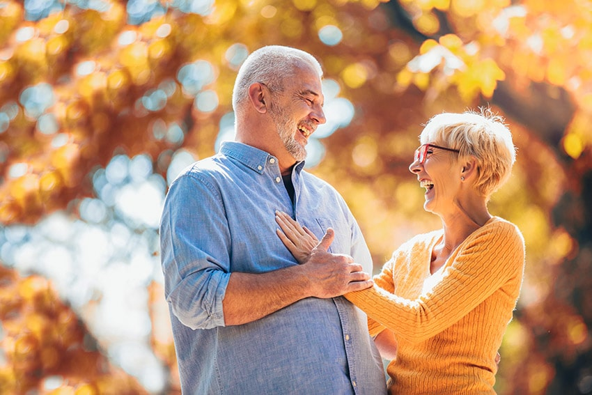Active senior couple walking in the park in the fall