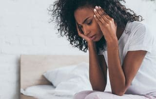 young woman sitting on the side of her bed with a headache