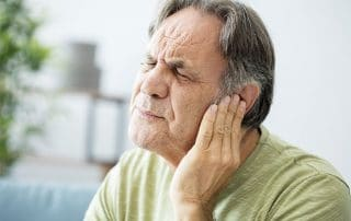senior man suffering from ringing in his ears