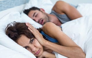annoyed woman covering her ears next to snoring husband
