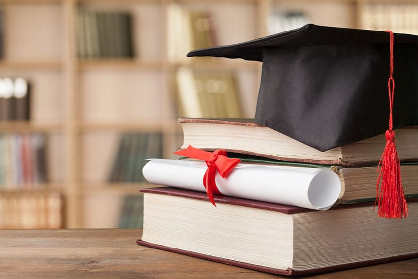graduate hat sitting on books in library