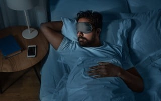 man with a sleep mask rest peacefully in bed