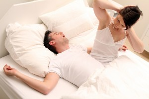 woman looking at her husband, snoring