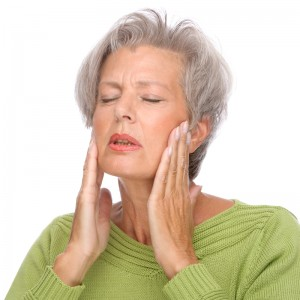 Senior woman touching her jaw, in some pain.