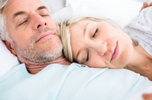 Older couple sleeping comfortably together in bed
